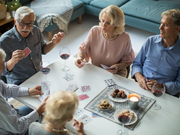 Seniors PLaying Cards | Retirement Community vs Aging in Place | Cottage Grove Place